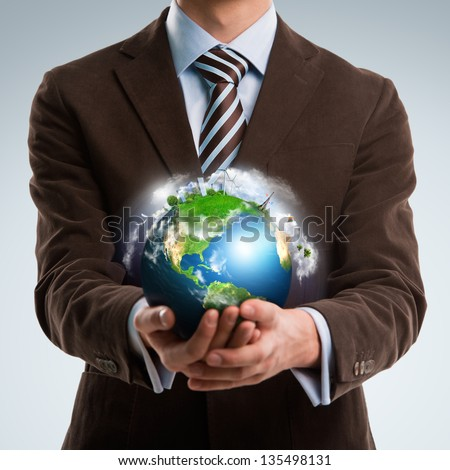 Businessman keeps the world in his hands - stock photo