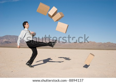 Businessman kicking boxes in the air - stock photo
