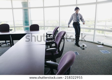 Businessman kicking soccer ball in office - stock photo