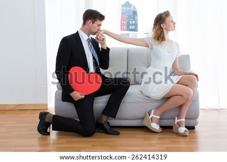 Businessman kissing his girlfriend hand on the living room - stock photo