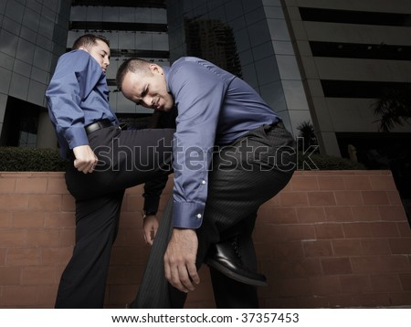 Businessman kneeing another businessman