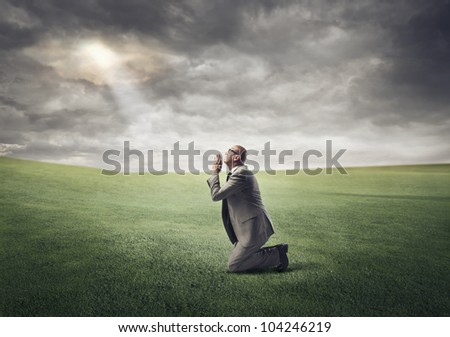 Businessman kneeling on a green meadow and praying - stock photo