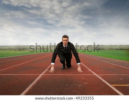 Businessman kneeling on a starting grid - stock photo