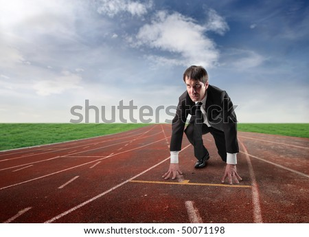 Businessman kneeling on the starting grid of a running track - stock photo
