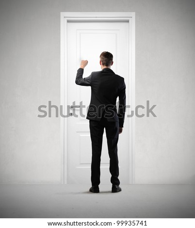 Businessman knocking at a door - stock photo