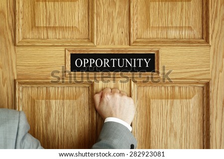 "Businessman knocking on a door to ""Opportunity"" office concept for aspirations, progress meeting or promotion - stock photo"
