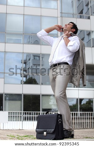 Businessman laughing on his cellphone outside an office building