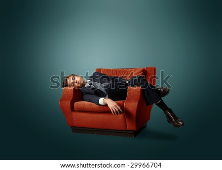 businessman laying on an armchair - stock photo