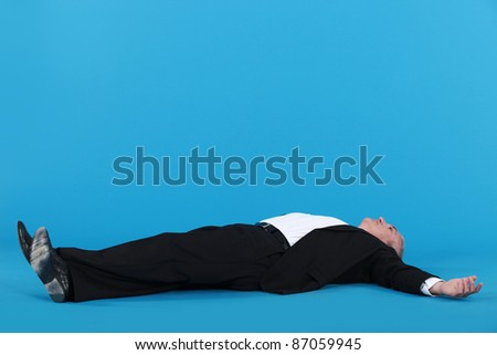 Businessman laying on floor - stock photo