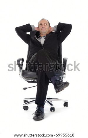 businessman leaning back in his desk chair - stock photo