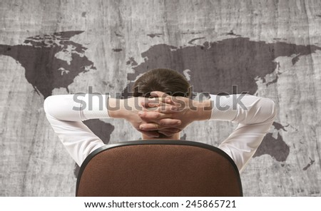 Businessman leaning back looking at world map  - stock photo
