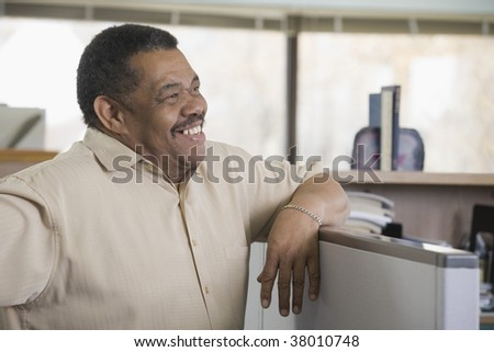Businessman leaning on a cubicle in an office - stock photo
