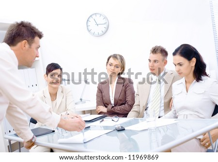 Businessman leaning on desk, explaining to four colleagues sitting in front of. - stock photo