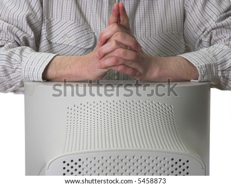 Businessman leaning on desktop PC monitor with his hands together.