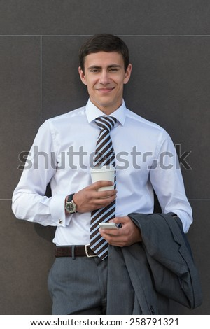 Businessman Leaning on Modern Office Building Wall With Coffee Using Mobile Phone - stock photo