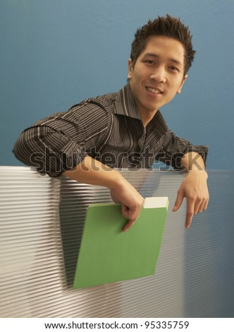 Businessman leaning over cubicle wall - stock photo