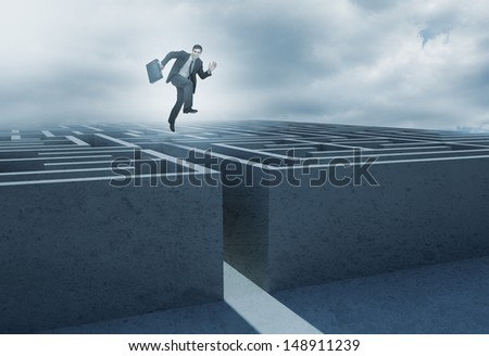 Businessman leaping above a maze and smiling at camera - stock photo