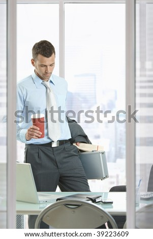 Businessman leaving office, holding suitcase and coffee cup in hand.