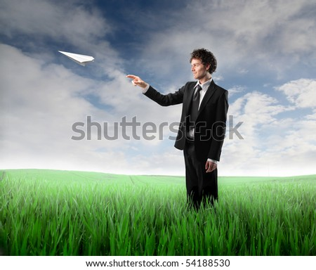 Businessman letting an airplane made of paper fly over a green meadow - stock photo