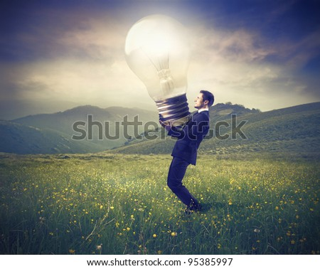 Businessman lighting up a green meadow with a giant light bulb - stock photo