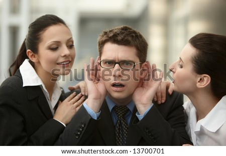 Businessman listening to advice from two woman whispering to ear in the office - stock photo