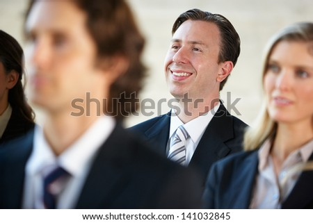 Businessman Listening To Speaker At Conference - stock photo