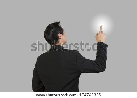 Businessman look and point high on gray background