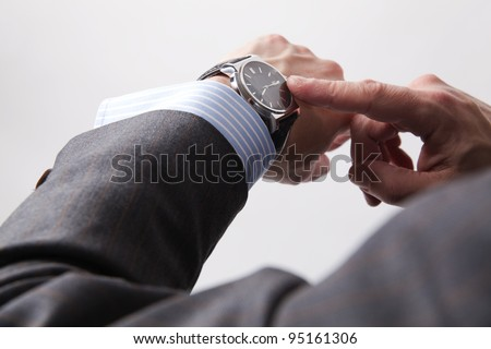 Businessman look his watch, isolated on a grey background