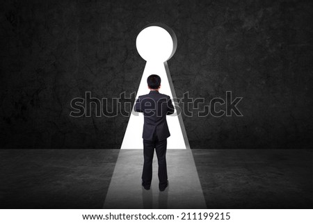 businessman looking against old grunge black wall with key hole - stock photo