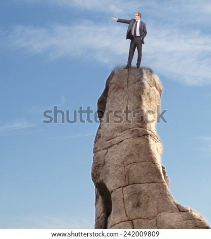Businessman looking and showing finger at far away in future for other stuff people against blue sky with clouds Business concept Man leader boss person stand on high hill stone mountain texture  - stock photo