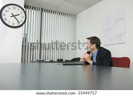 Businessman looking at a clock in an office - stock photo