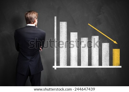 businessman looking at a declining info graph - stock photo