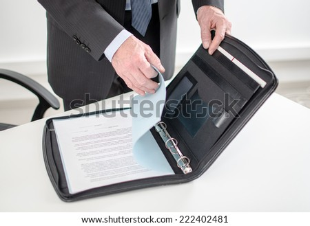 Businessman looking at a document in his briefcase