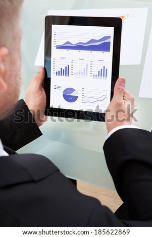 Businessman looking at a series of graphs on his tablet computer as he works at his desk  over the shoulder view of the screen