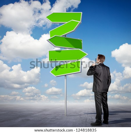 Businessman looking at an arrow sign