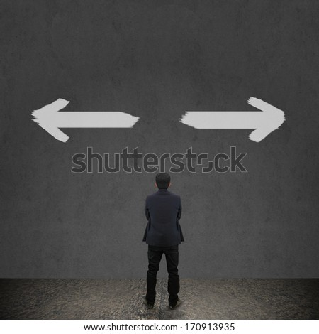 Businessman looking at arrows on the wall - stock photo