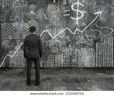 businessman looking at business concept doodles hand-drawn on concrete wall and floor background - stock photo