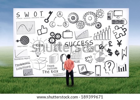 Businessman looking at business strategy on whiteboard. Shot outdoors - stock photo