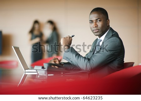 Businessman looking at camera, colleagues on background - stock photo