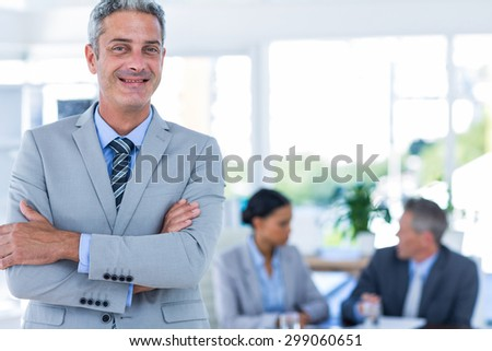 Businessman looking at camera with his colleagues behind him in office - stock photo
