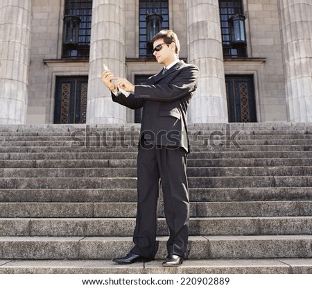 Businessman looking at cell phone on stone stairs - stock photo
