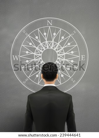 businessman looking at compass over grey background - stock photo