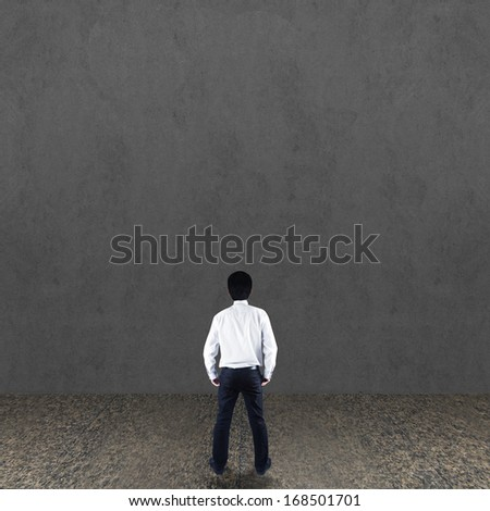 Businessman looking at concrete wall
