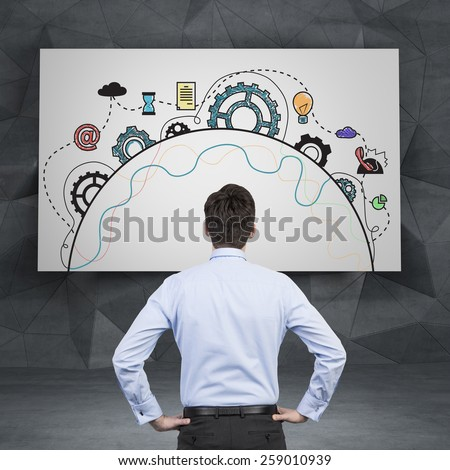 businessman looking at drawing business icons on desk - stock photo
