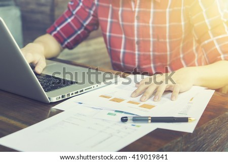 businessman looking at financial data with graphics and charts while work on a laptop computer, young entrepreneur analyzing his notebook, male freelancer work in cafe,selective focus,vintage color - stock photo