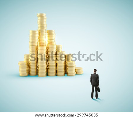 businessman looking at gold coin city - stock photo