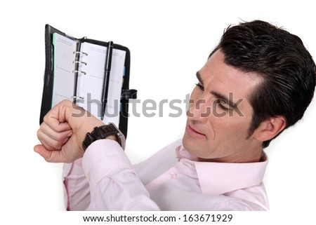 businessman looking at his agenda and his watch - stock photo