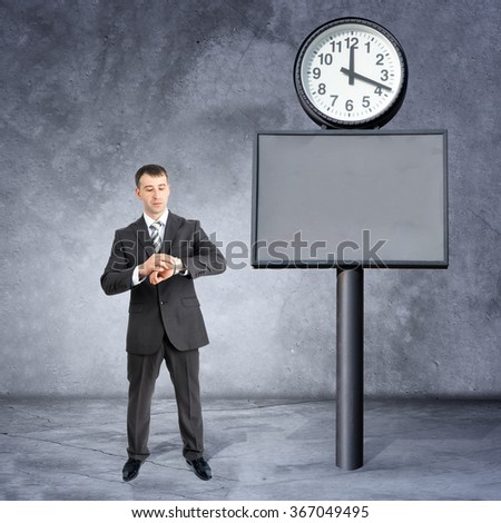 Businessman looking at his hand near big clock - stock photo