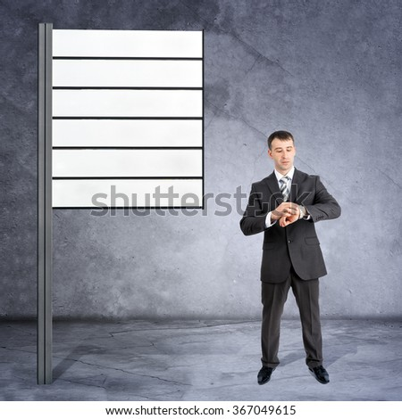 Businessman looking at his hand near road sign - stock photo