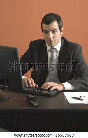Businessman looking at his laptop computer at his desk. Vertically framed photograph. - stock photo